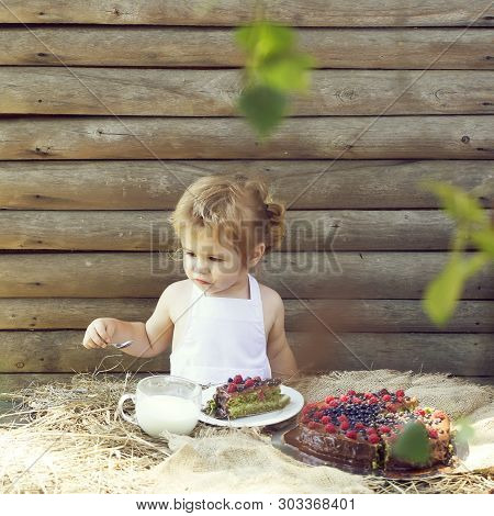 Cute Little Boy In White Pinafore Eats Fruit Cake And Cup Of Milk At Table Outdoors On Wooden Backgr