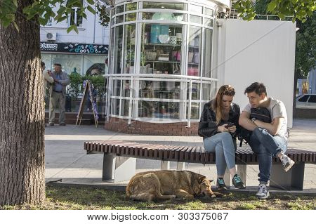 Nizhny Novgorod, Russia, - May 12, 2019: A Loving Couple Is Sitting On A Bench. Red Dog Lying At The