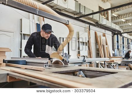Sawing Up Of A Wooden Board On A Sliding Table Saw. Woodworking And Carpentry Production. Furniture