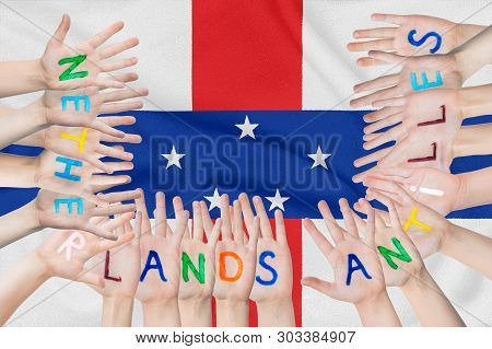 Inscription Netherlands Antilles On The Children's Hands Against The Background Of A Waving Flag Of