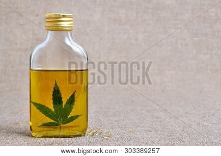 Cannabis And Hemp Oil In A Transparent Bottle. Marijuana Extract, Medicine And Food Supplement