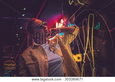 Portrait Of Pensive Trendy Woman In Neon Lights With Darkness Around.