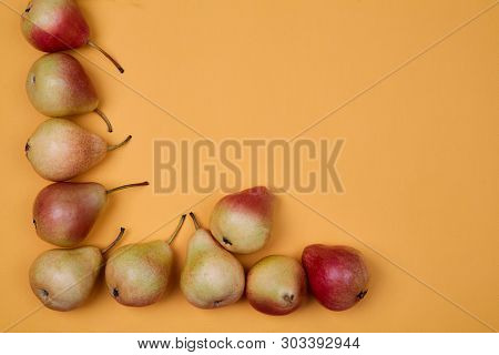 Ripe Juicy Pears Placed On Orange Background. Colorful Fruit Pattern Or Background.