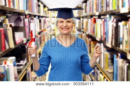 graduation, education and old people concept - happy senior graduate student woman in mortar board with diploma over library background