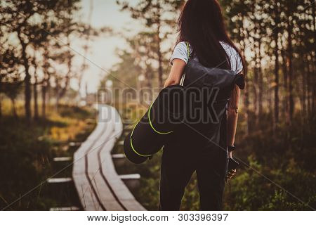 Skinny Young Woman Is Hiking By The Wooden Path In The Middle Of Lush Pine Forest.