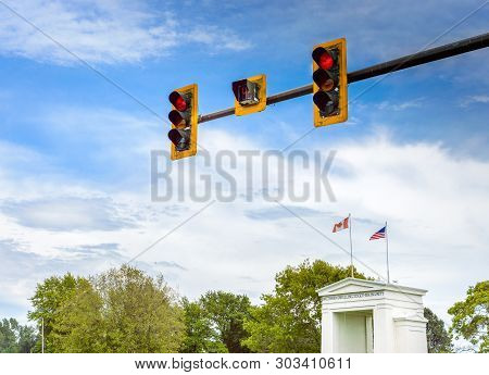 Red Traffic Lights Above Canada And Usa Flags On Top Of Peace Arch Monument At International Border