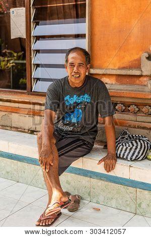 Dusun Ambengan, Bali, Indonesia - February 25, 2019: Clan Compound. Closeup Of Sitting Man With Oran