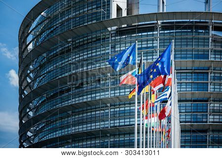 Facade Of European Parliament With Flags Of All Member States Of The European Union Waving In Calm W