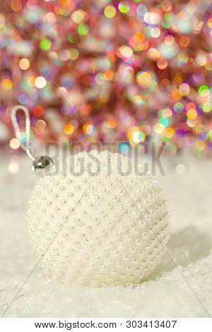 Christmas Decoration. Ball With Nacre Pearls On A Snow And Beautiful Blurred Colorful Background Of