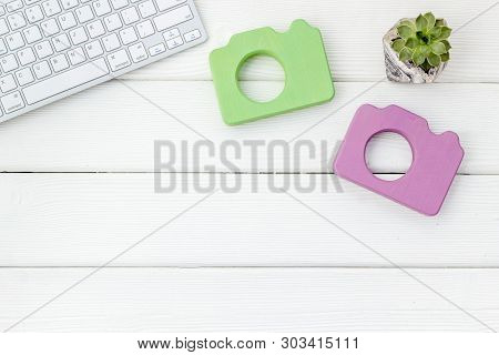 Office Desk Of Blogger With Camera, Keyboard And Plant On White Wooden Background Top View Copy Spac