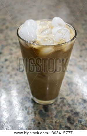 Iced Cold Brew Coffee In Tall Pounder Glass On Granite Countertop With Coffee Swirls In It