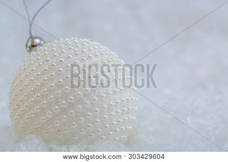 Holiday Decoration.white Ball With Nacre Pearls On A Snow And Beautiful Blurred Background Of Glitte