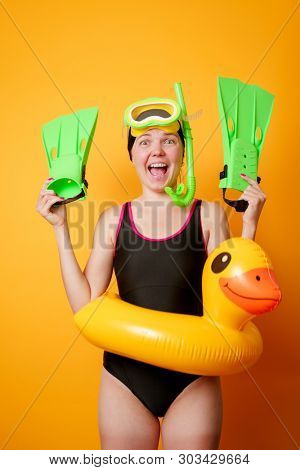 Photo of smiling woman with flippers in hands, swimming mask and with life preserver on empty orange background