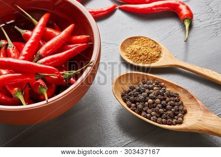 Still life with different peppers (whole black dry and powdered mix peppers in a wooden spoons, fresh red chile peppers in a bowl) on a gray background. Top view.