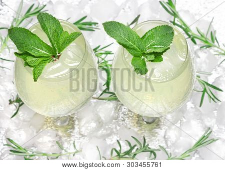 Chilled Drink With Mint Leaves In Glass Cocktail Goblets On Ice Cubes. Summer Beverage. Bar Menu. Co