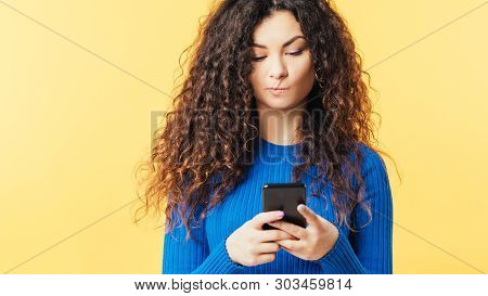Young Woman Looking At Smartphone. Pursed Lips. Skepticism Doubt Facial Expression. Suspicious Incre