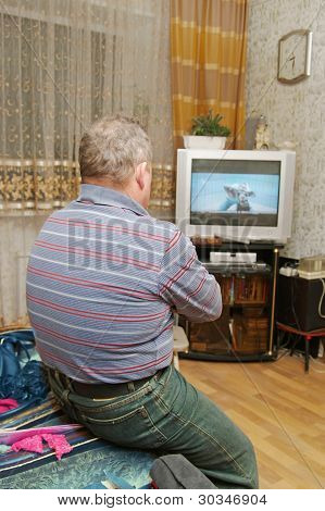 A Man Watching  Screen Of His Television.