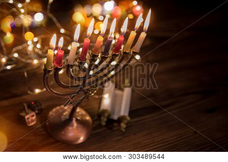 Concept of jewish holiday Hanukkah with menorah (traditional candelabra) and burning candles.