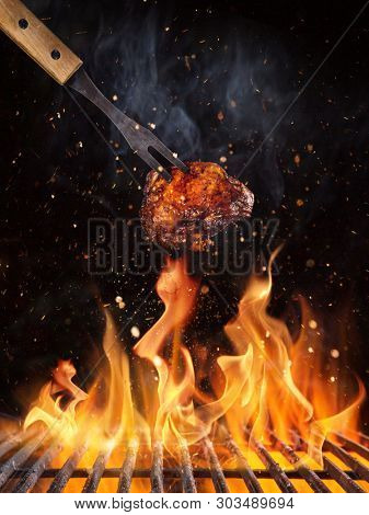 Tasty chicken piece on the grill with fire flames