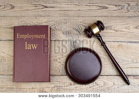 Law Concept - Employment Law. Open Law Book With A Wooden Judges Gavel On Table In A Courtroom Or La