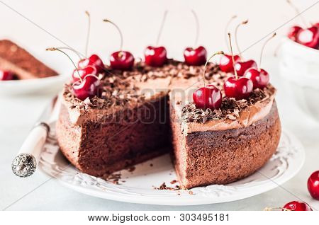 Sliced Chocolate Cake Decorated With Chocolate Shavings And Sweet Cherries