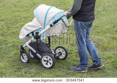 The Father Walks With Carriage,bottom View Only Legs. Bright Mint Stroller And Legs In Jeans, Walkin