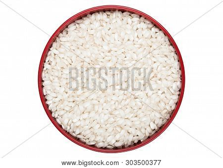 Red Bowl Of Raw Organic Arborio Risotto Rice On White Background. Top View