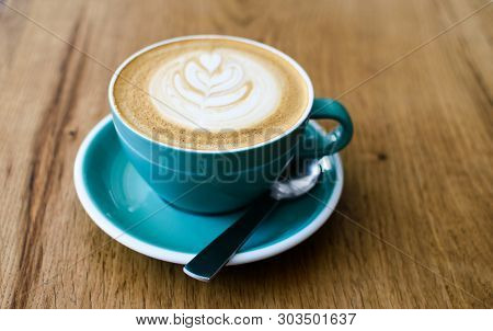 A Cup Of Cappuccino With Latte Art And Spoon On Wooden Background. Beautiful Foam, Greenery Ceramic