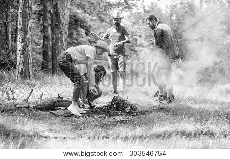Friends Working As Team To Keep Bonfire. Company Camping Forest Prepare Bonfire For Picnic. Add Some