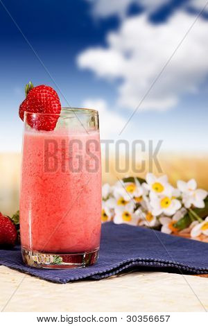 A fresh summer strawberry drink in an outdoor setting