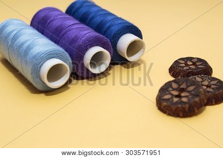 Concept For Needlework, Stiching, Embroidery. Sewing Multicolored Threads And Brown Buttons On Yello