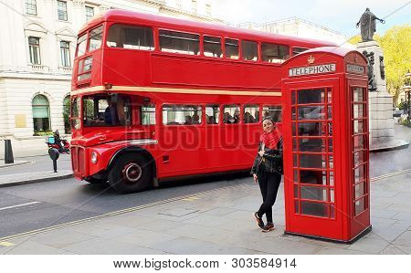 Woman Traveling To London, Standing Near A Telephone Box And A Red British Bus.
