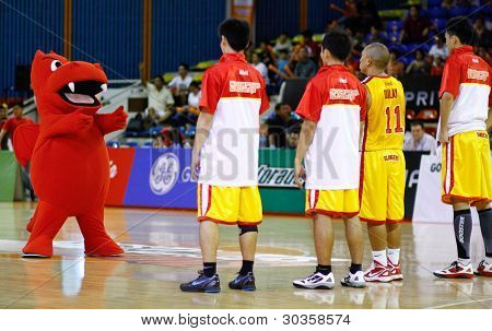 KUALA LUMPUR - FEBRUARY 19: The Dragons' mascot mocks gun firing at the  Slingers players at the start of the ASEAN Basketball League match on February 19, 2012 in Kuala Lumpur, Malaysia. Dragons won 86-71.