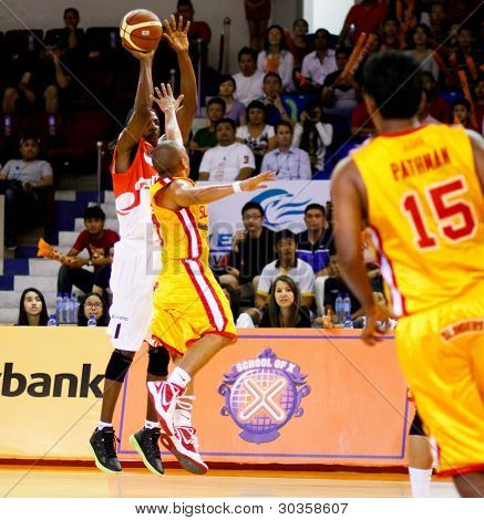 KUALA LUMPUR - FEBRUARY 19:Malaysian Dragons' Tiras Wade (white) makes a jumpshot in at the ASEAN Basketball League match against Singapore Slingers on Feb 19, 2012 in Kuala Lumpur, Malaysia. Dragons won 86-71.