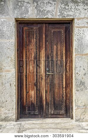 Rustic Wooden Doors Are Closed In The Old Stone Wall Of Spanish Mission San Juan Capistrano In San A