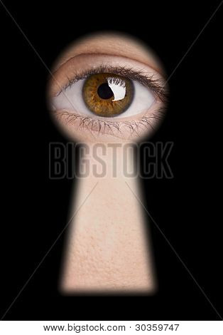 Eye looking through a blured black keyhole