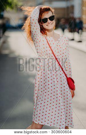 Mirthful Young Lady Strolls On Street, Has Long Red Hair, Wears Stylish Dress, Sunglasses, Enjoys Su