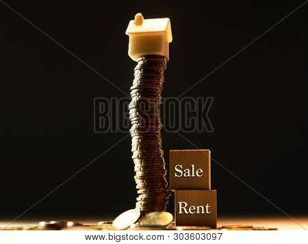 Mini house on stack of coins, wood block with word sale and rent concept of Investment property.