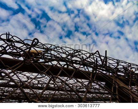 View Of The Sky With Clouds Due To Barbed Wire. The Concept Of Educating Respectable Law-abiding Cit