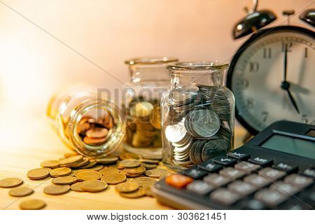 Calculator With Coin In Currency Glass Jar And Clock On Wooden Table. Compound Interest Rate Calcula