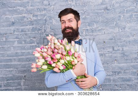 Macho getting ready romantic date. Waiting for darling. Tulips for sweetheart. Man well groomed wear tuxedo bow tie hold flowers bouquet. Invite her dating. Romantic man with flowers. Romantic gift. poster
