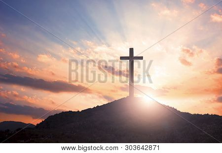 Surrender Concept: Silhouette Of Crucifix Cross On Mountain At Sunset Time With Holy And Light Backg