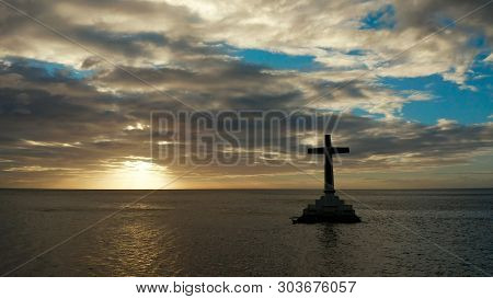 Catholic Cross In Sunken Cemetery In The Sea At Sunset, Aerial Drone. Large Crucafix Marking The Und