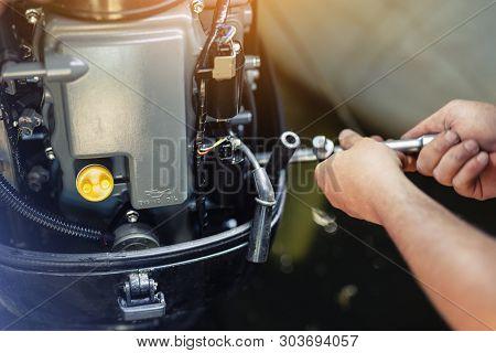 Mechanic Repairing Inflatable Motorboat Engine At Boat Garage. Ship Engine Seasonal Service And Main