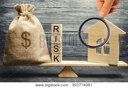 Money Bag, Blocks With The Word Risk And A Wooden House On The Scales. The Concept Of Losing Money W