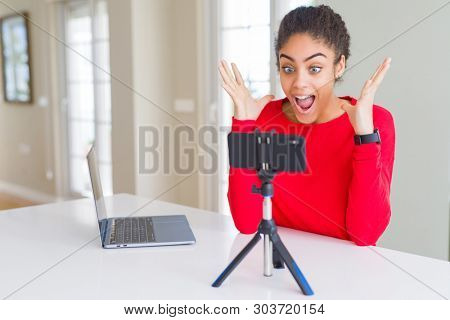 poster of Young african american woman doing video call using smartphone camera celebrating crazy and amazed for success with arms raised and open eyes screaming excited. Winner concept