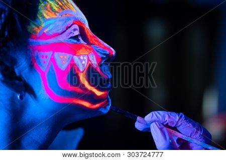Ultraviolet black light glowing bodyart processing on young womans face. Pink and purple dyes in cold blue light poster