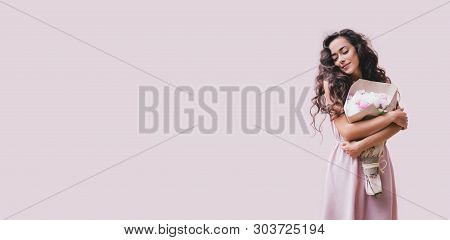 Young Beautiful Woman With Long Curly Hair In A Pink Dress With A Big Bouquet Of Peonies On A Pink B