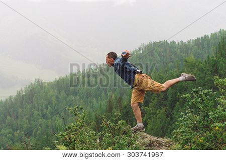 Mad Tourist On Mountain Peak. Joyful Traveler Stands On One Leg Over Abyss. Crazy Man Is Jumping On