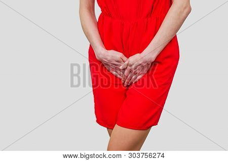 Woman in a red dress holding hands between legs. Experiencing pain, discomfort. Women's health, gynecology. poster
